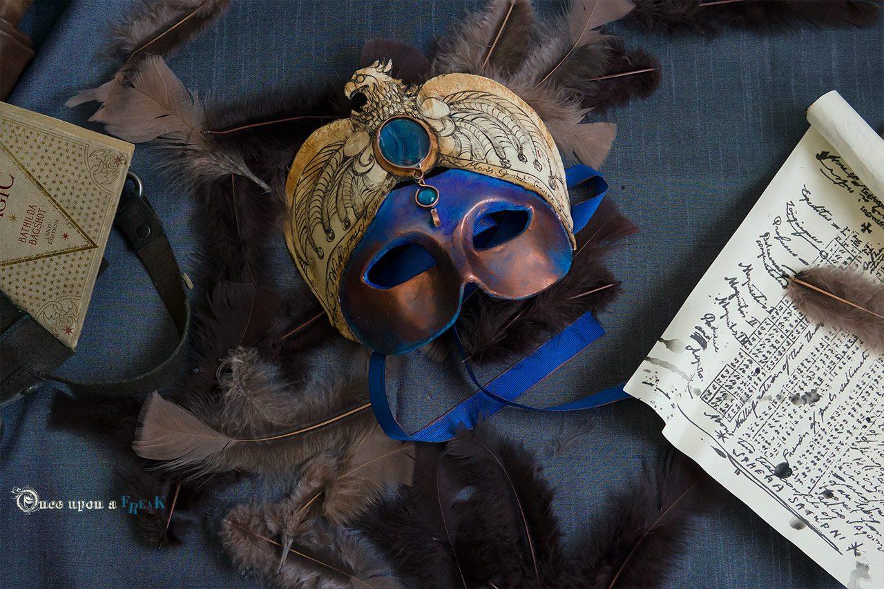 máscara harry potter junto a pergamino y libro Una historia de la magia
